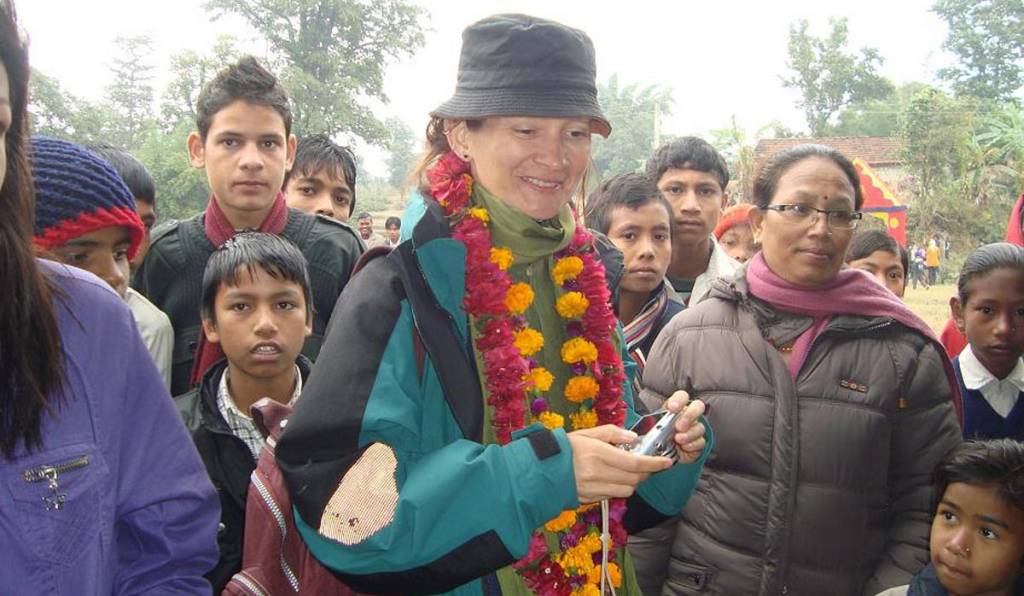 A foreign tourist happy with indigenous Tharu men, women and children  Homestays in Nepal
