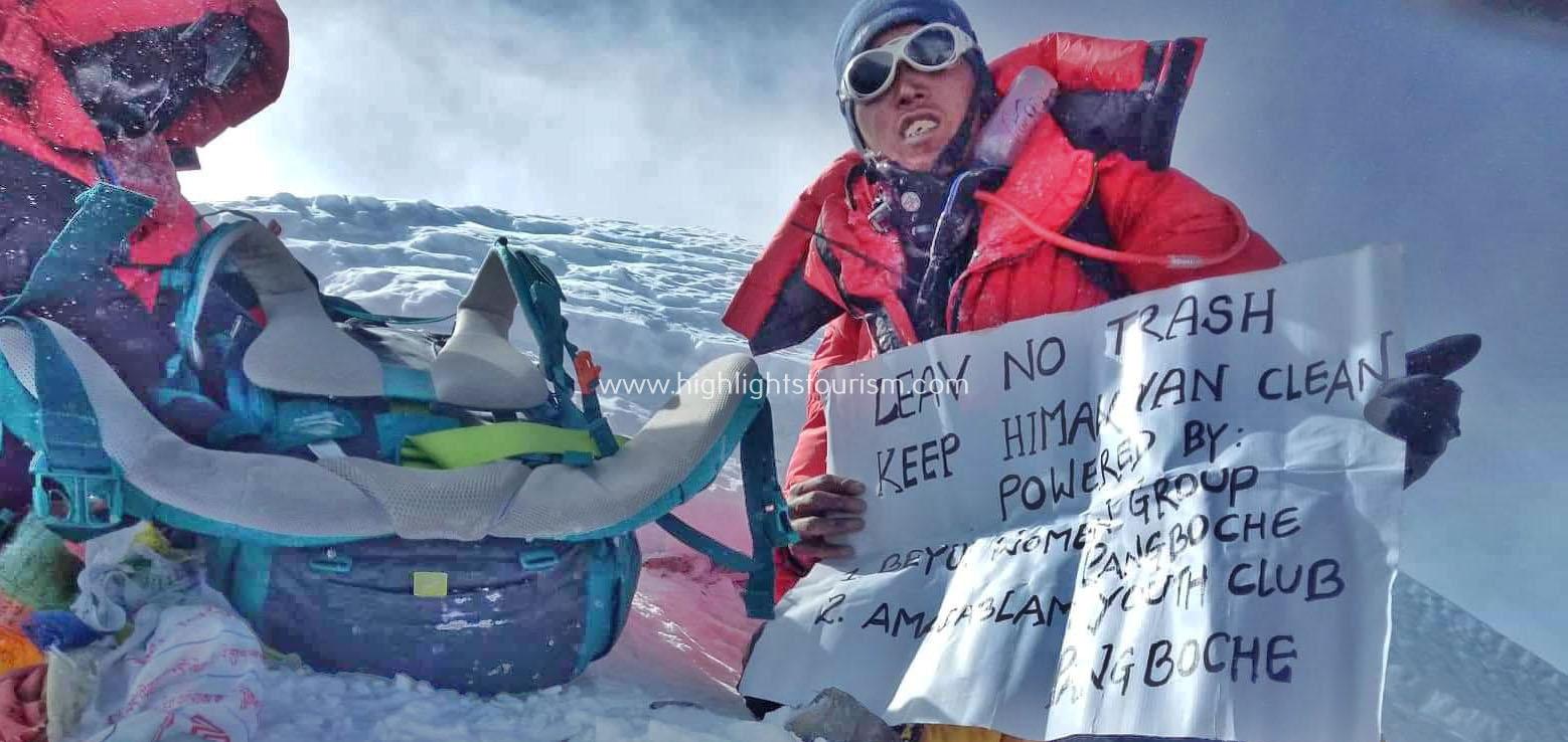 "Tamang at the peak holding placard with ""leave no trash""slogan"