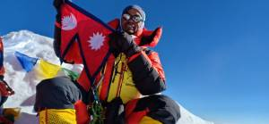 Climber on Everest with Nepali flag